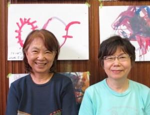 子どもたちの絵を背に足立隆子(右)海田みどりさん(左)